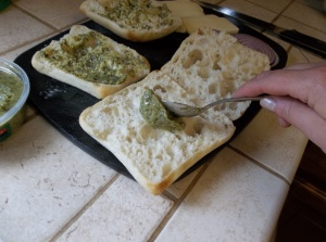 With the back of a spoon, take a generous tablespoon of pesto and brush the bread on all 4 pieces.