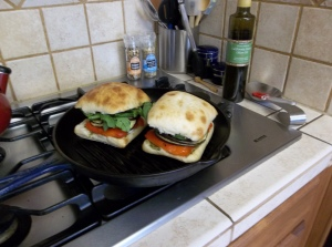 Brush a grill pan lightly with olive oil.  Get it hot.  Once heated, add the two sandwiches.